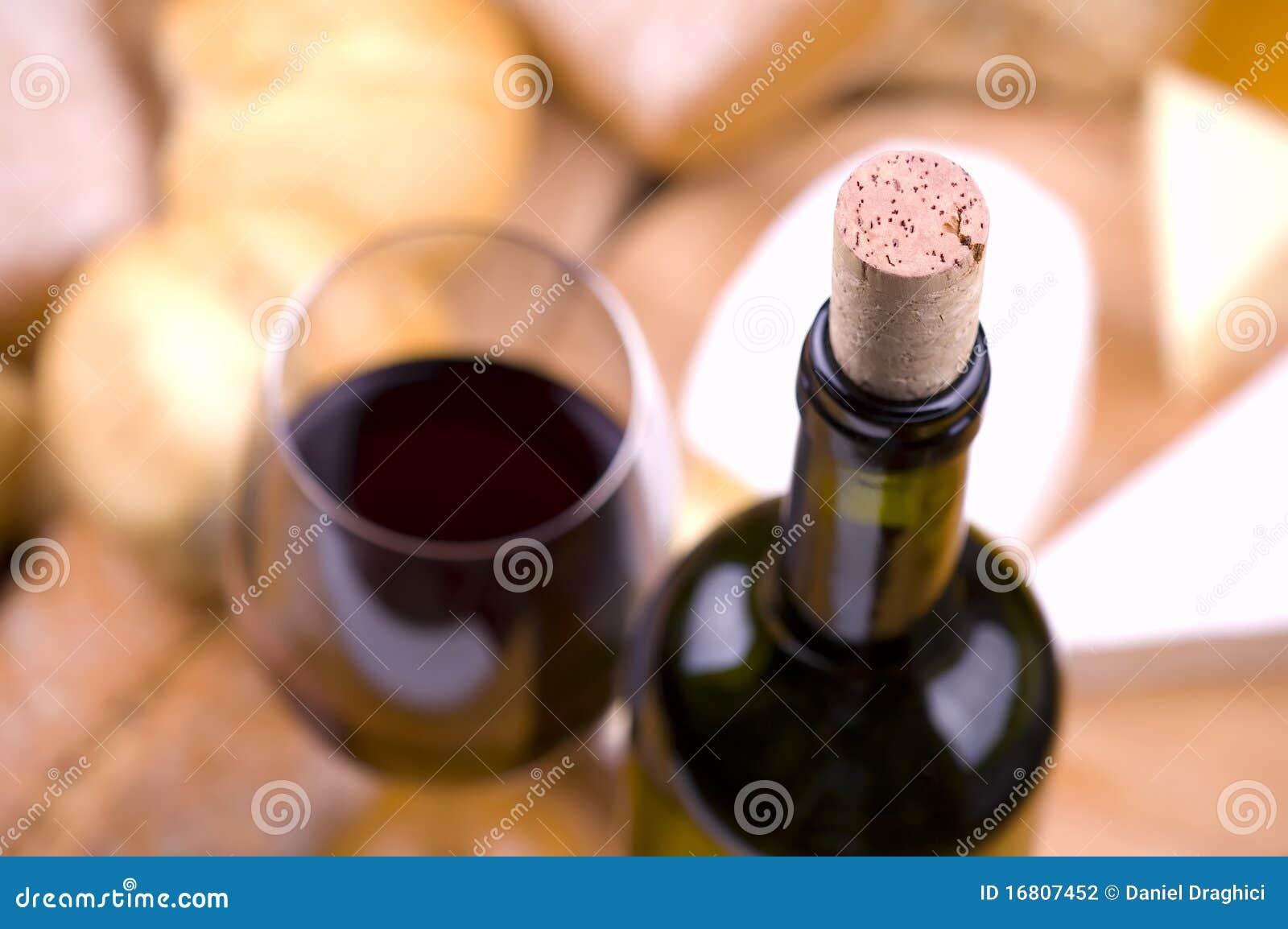Primer de la botella de vino con el alimento y el vidrio