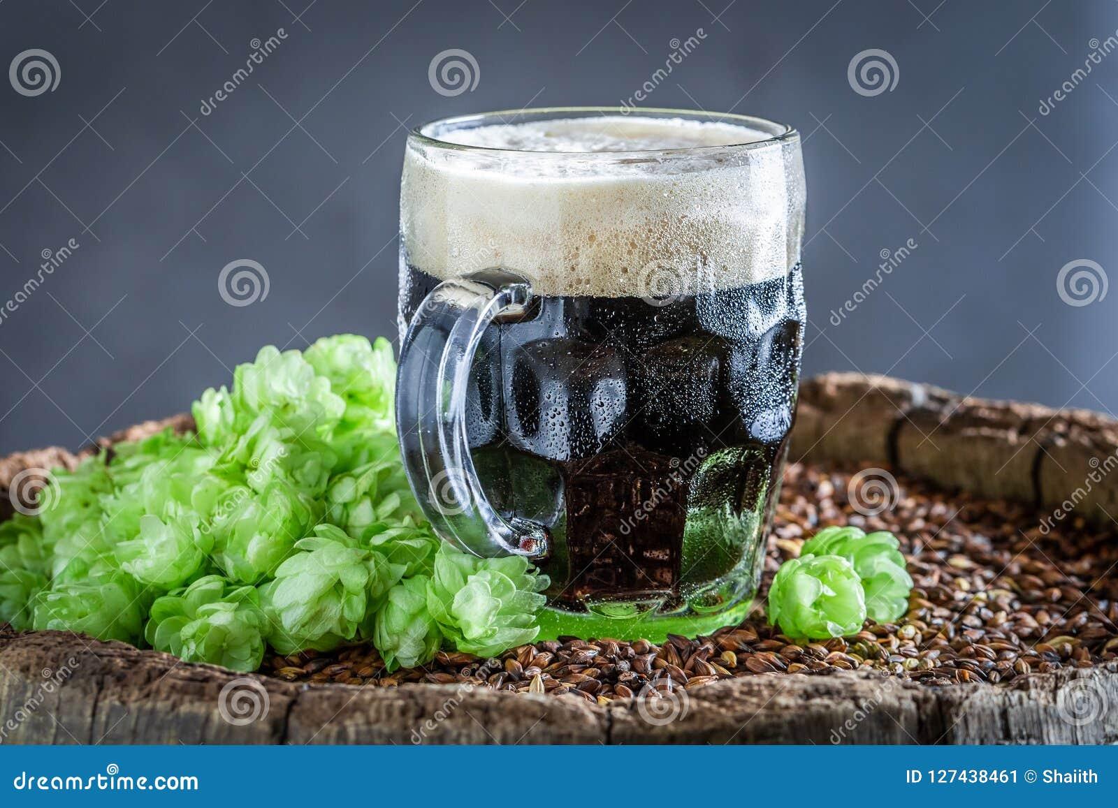 Primer de la cerveza oscura fría con la espuma blanca