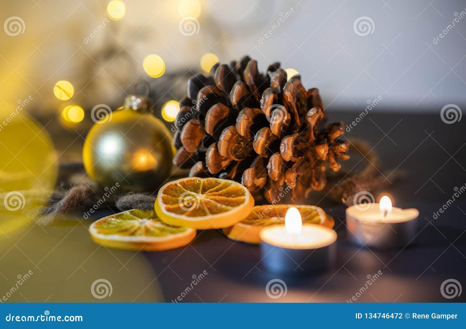 Primer de la decoración de la Navidad de un pinecone con el candel, la bola de la Navidad y las luces de la secuencia en un fondo