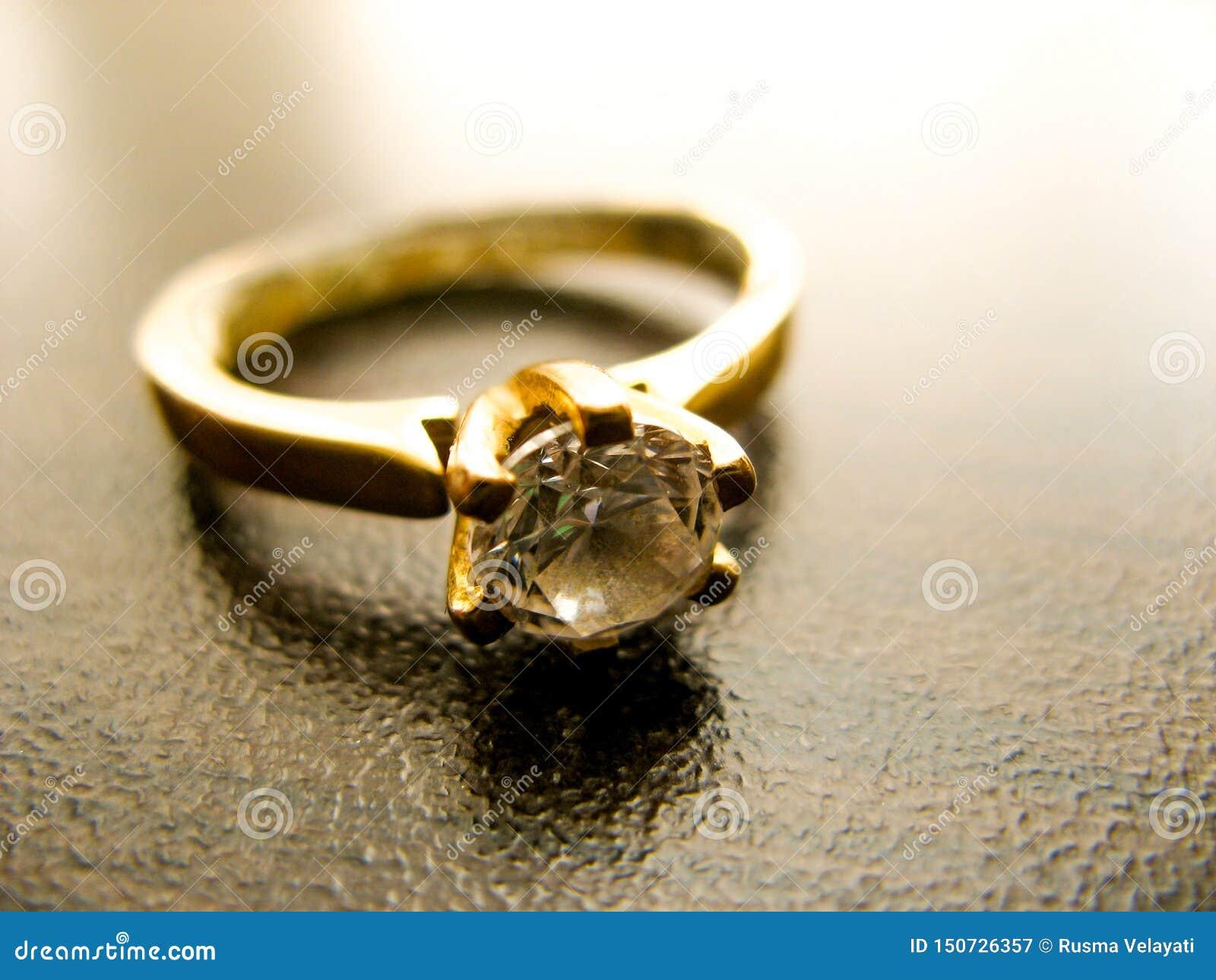 Primer de la gema del diamante del anillo de oro Boda o anillo de compromiso del oro adornado con el diamante