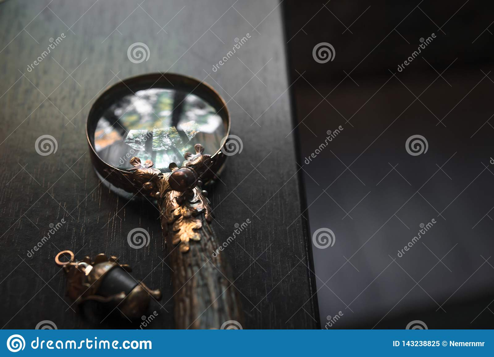 Primer de la lupa, lupa del vintage hecha a mano en el fondo de madera oscuro de la tabla, concepto de b?squeda, investigaci?n, d