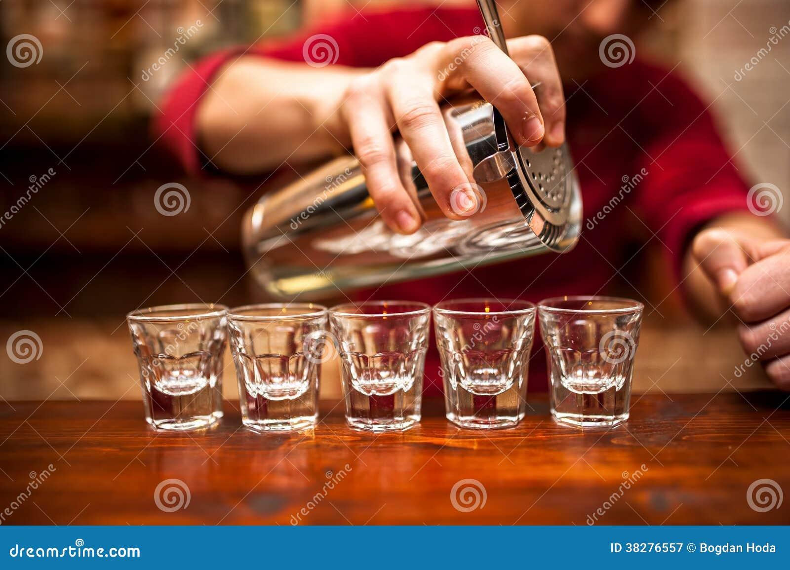 Primer de la mano del camarero que vierte la bebida alcohólica en club nocturno,