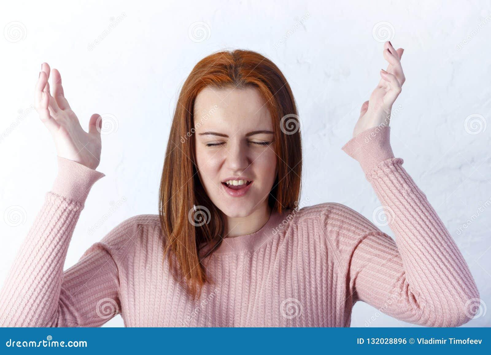Primer de la muchacha bonita infeliz desconcertada aislada en el fondo blanco que muestra emociones negativas