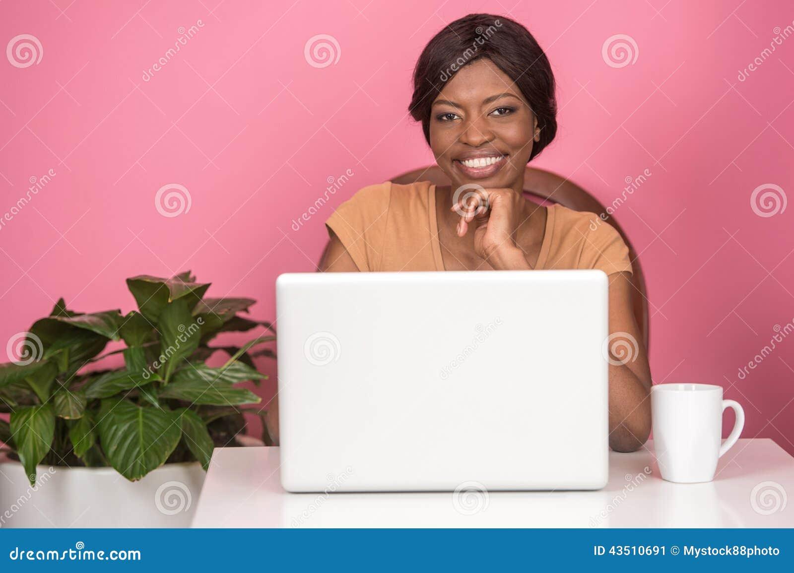 Primer de la mujer joven feliz que usa el ordenador portátil