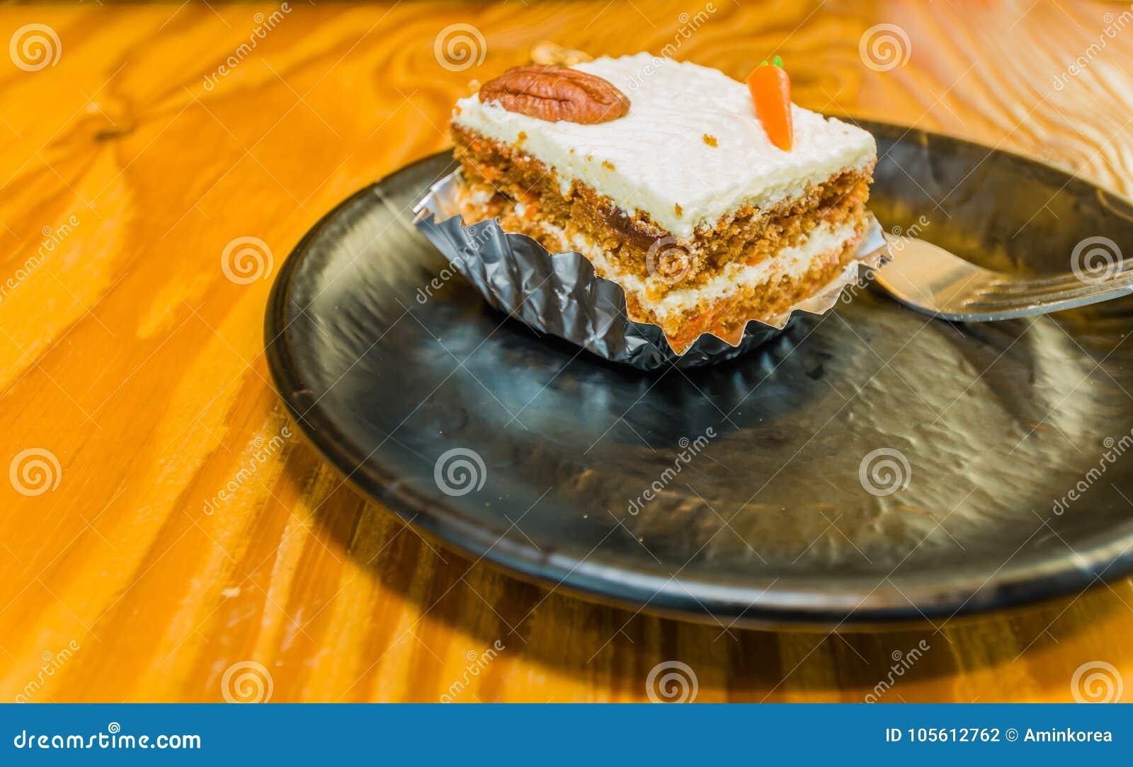 Primer de la pieza única de la torta de zanahoria adornada con una pacana