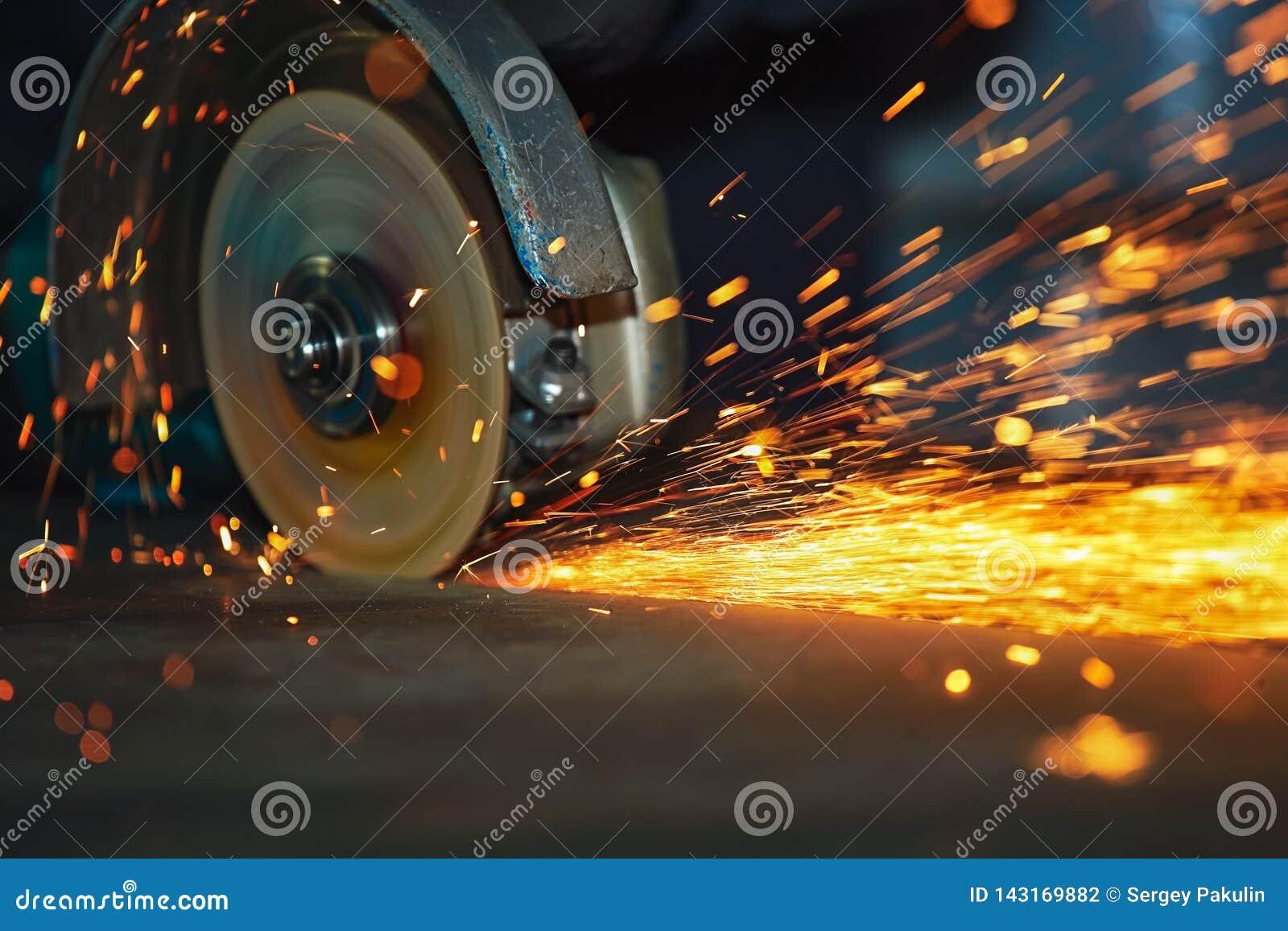 Primer de la rotación de la amoladora de ángulo del disco durante la operación Chispas brillantes de para corte de metales