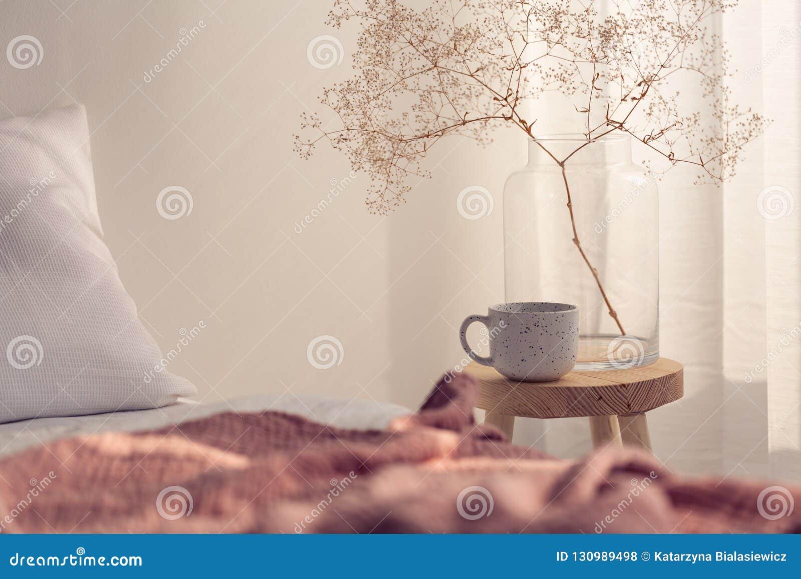 Primer de la taza y de la flor de café en el florero de cristal en la mesita de noche del interior brillante del dormitorio