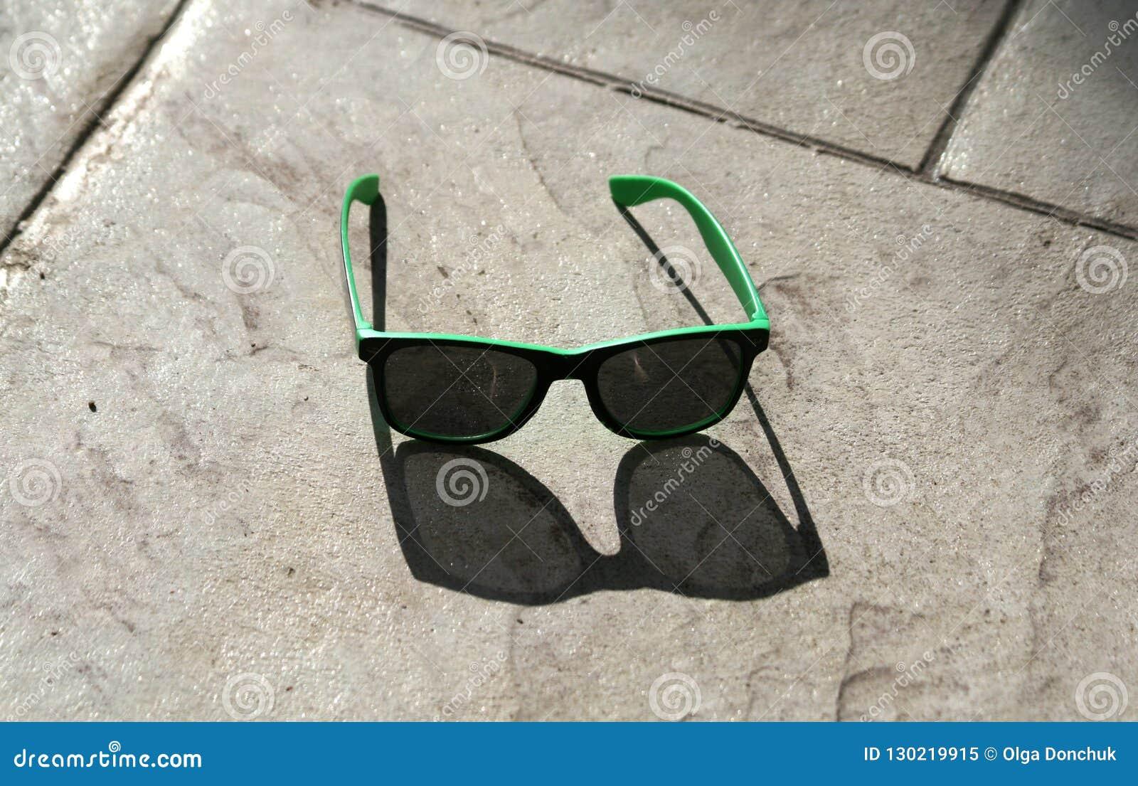 ba0c4376bf Gafas de sol verdes con las lentes oscuras que ponen en una pavimentadora  beige