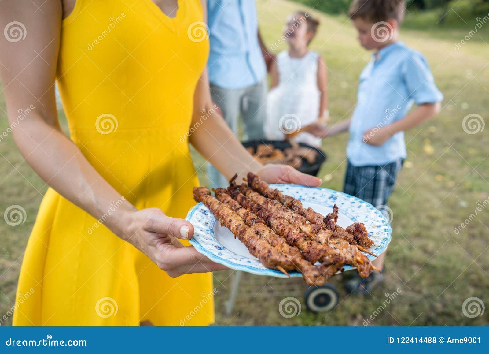 Primer de las manos de la mujer que sostienen una placa con los pinchos asados a la parrilla del filete