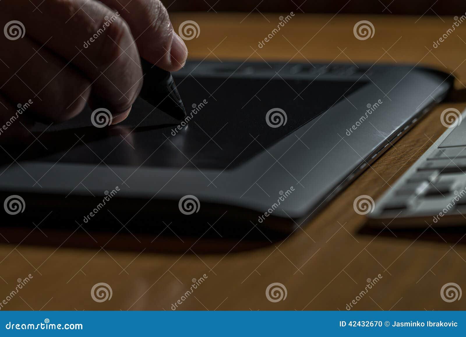 Primer de las manos que dibujan en la tableta gráfica