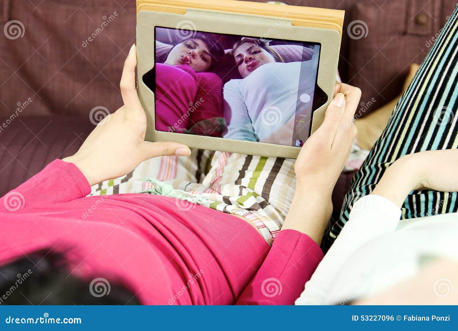 Primer de las muchachas que juegan que toma la imagen con la tableta