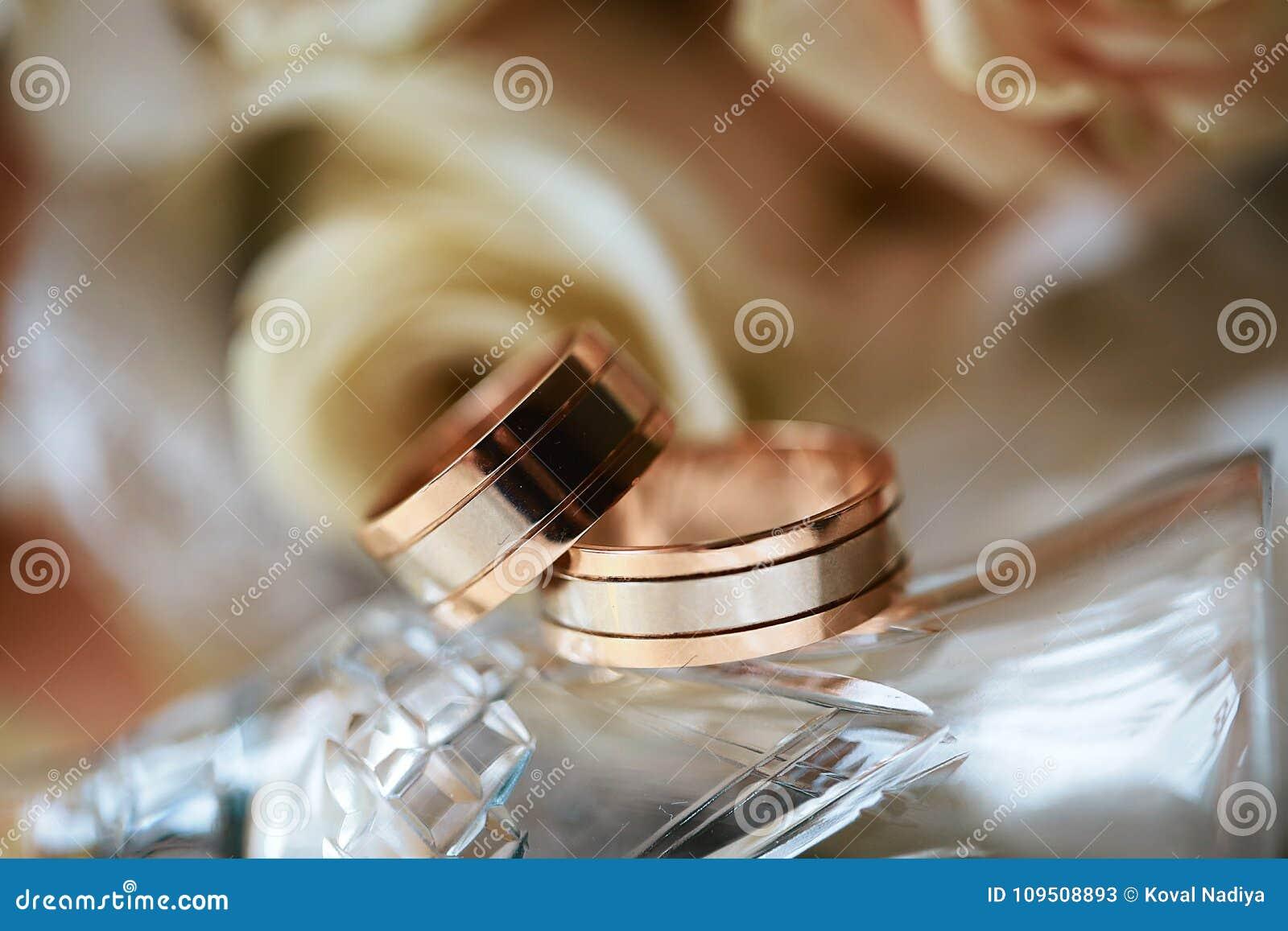 Primer de los anillos de bodas en el fondo de las rosas y del vidrio, accesorios de la boda