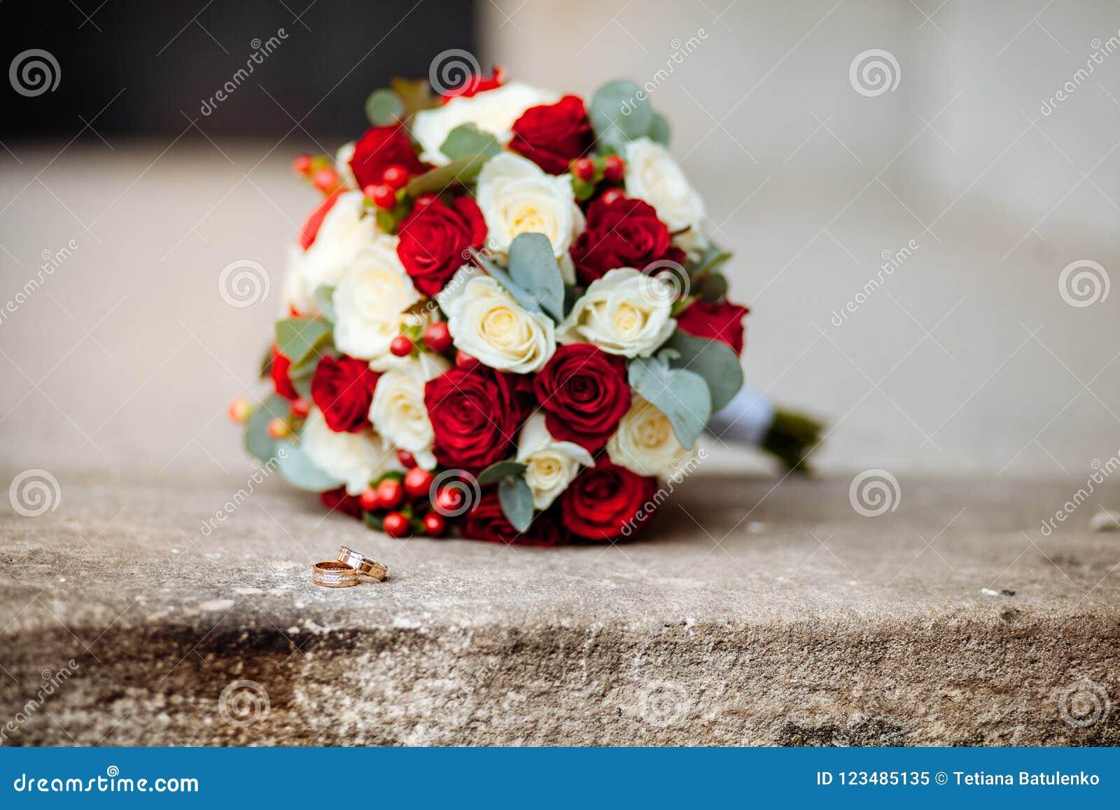 Primer de los anillos de bodas en el ramo de la boda del fondo de rosas de bayas y de verdes con lavanda