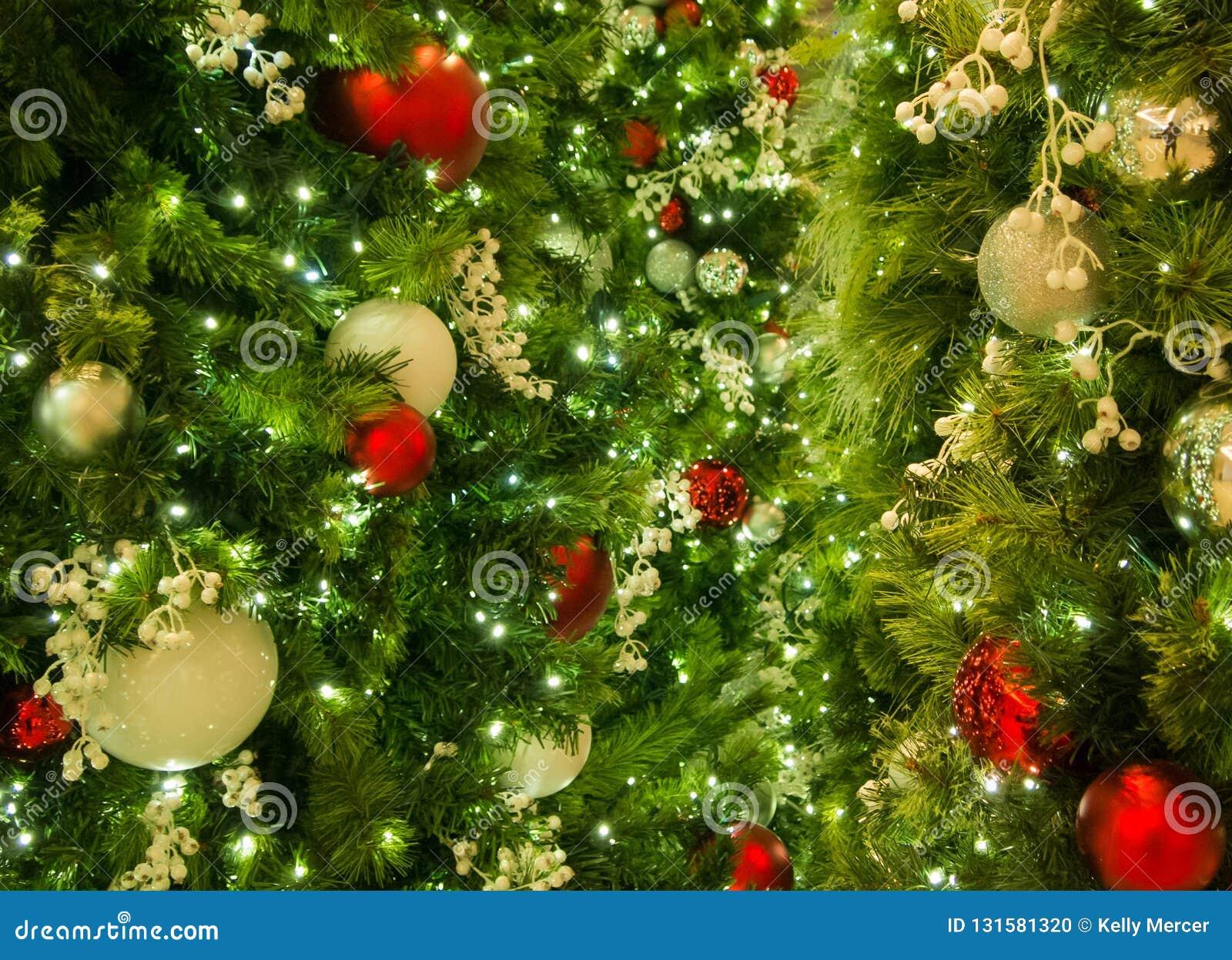 Primer de los ornamentos mezclados de la Navidad en árbol con las luces en marco
