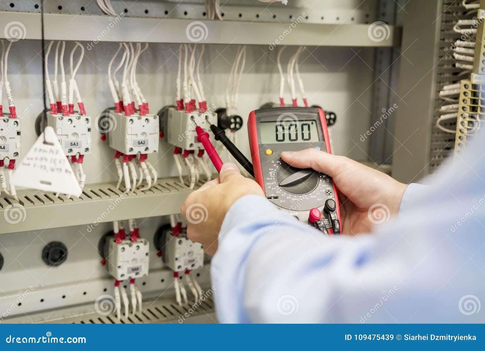 Primer de manos con el multímetro en panel de control eléctrico El ingeniero prueba la caja eléctrica de la automatización