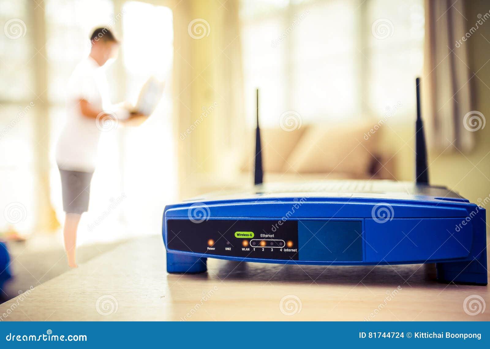 Primer de un router inalámbrico y de un hombre joven que usa el ordenador portátil y los ordenadores portátiles en sala de estar