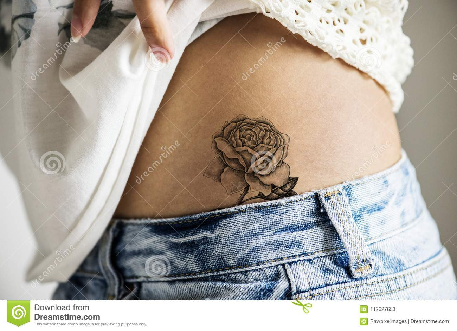 Primer De Un Tatuaje Más Bajo De La Cadera De Una Mujer Imagen De