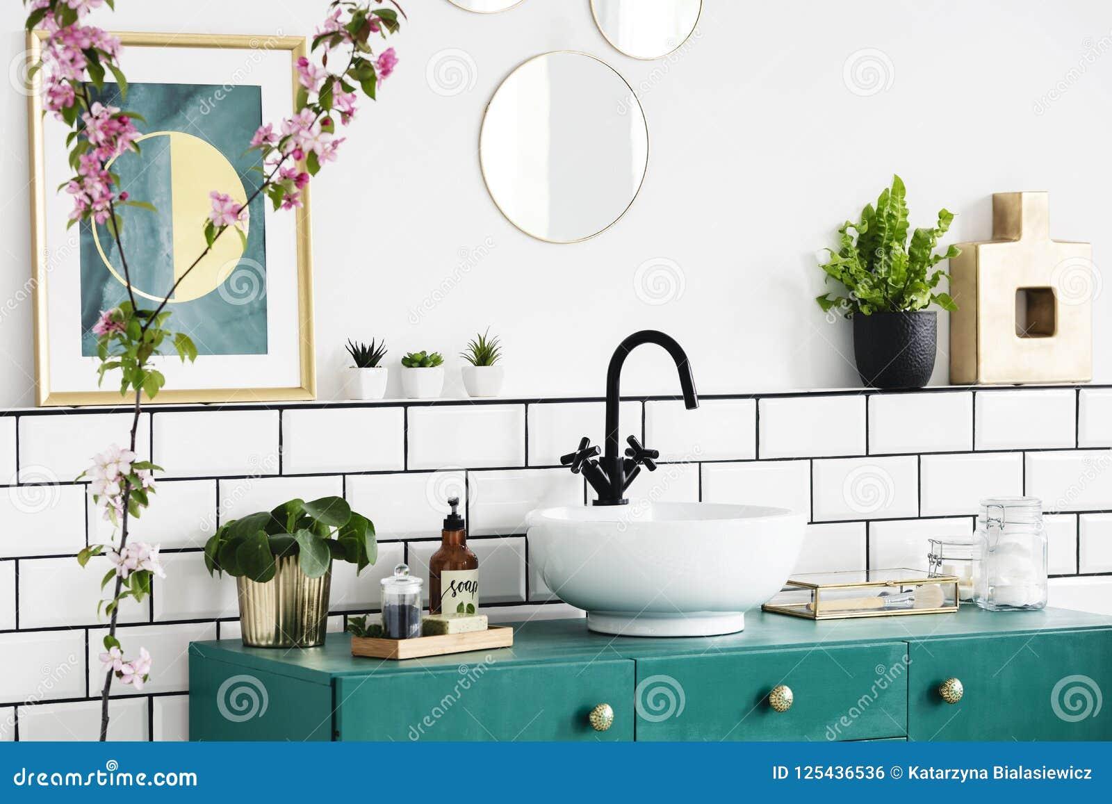Primer de una flor, gráfico en la pared y lavabo en un armario de la turquesa Foto verdadera