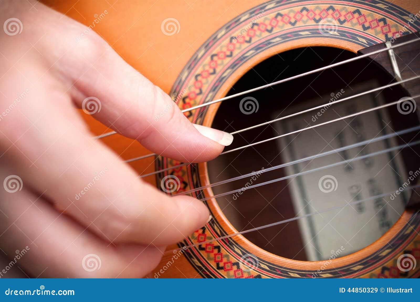 Primer de una mano del guitarrista con la guitarra