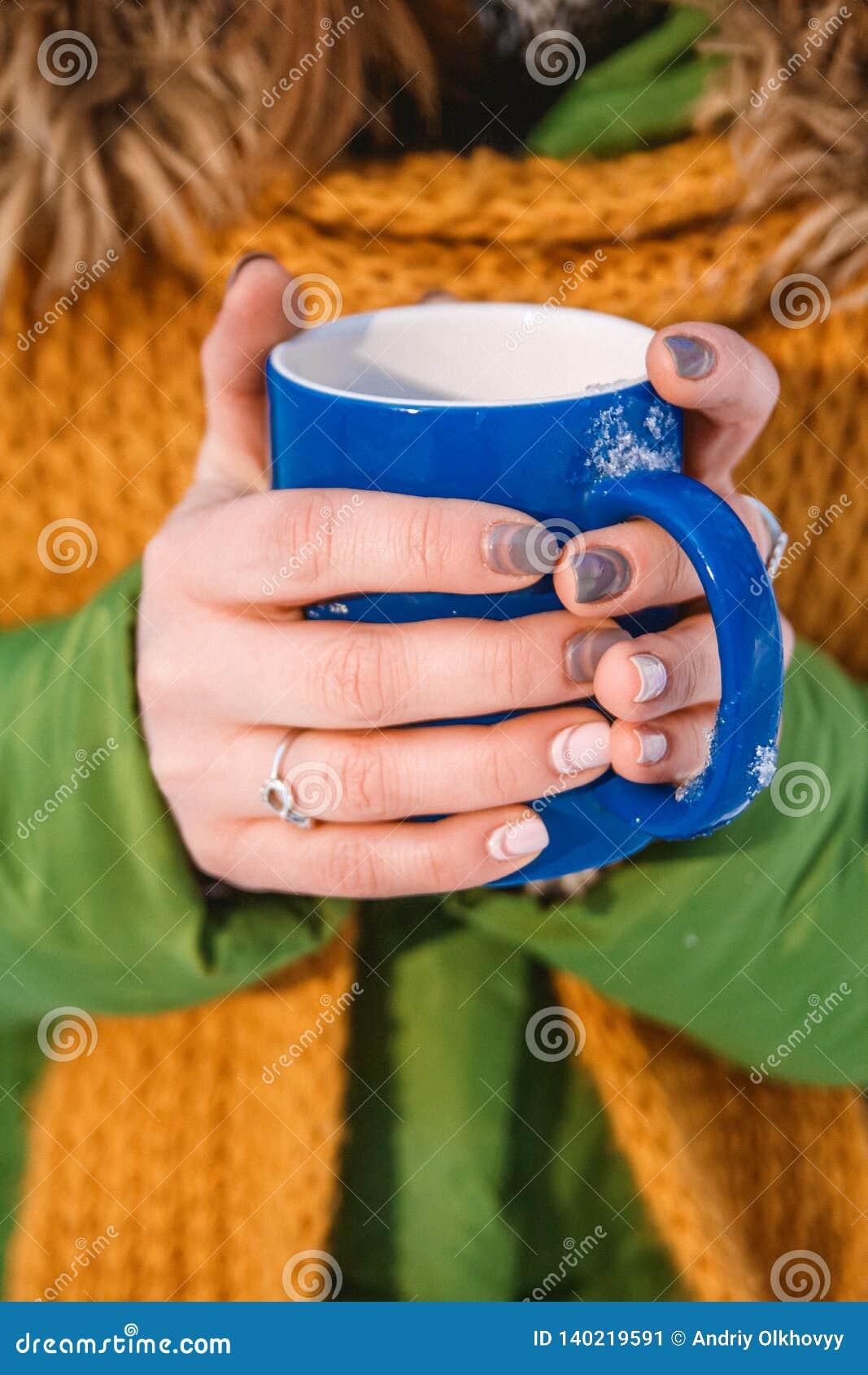 Primer de una mano del ` s de la mujer que sostiene una taza de café caliente