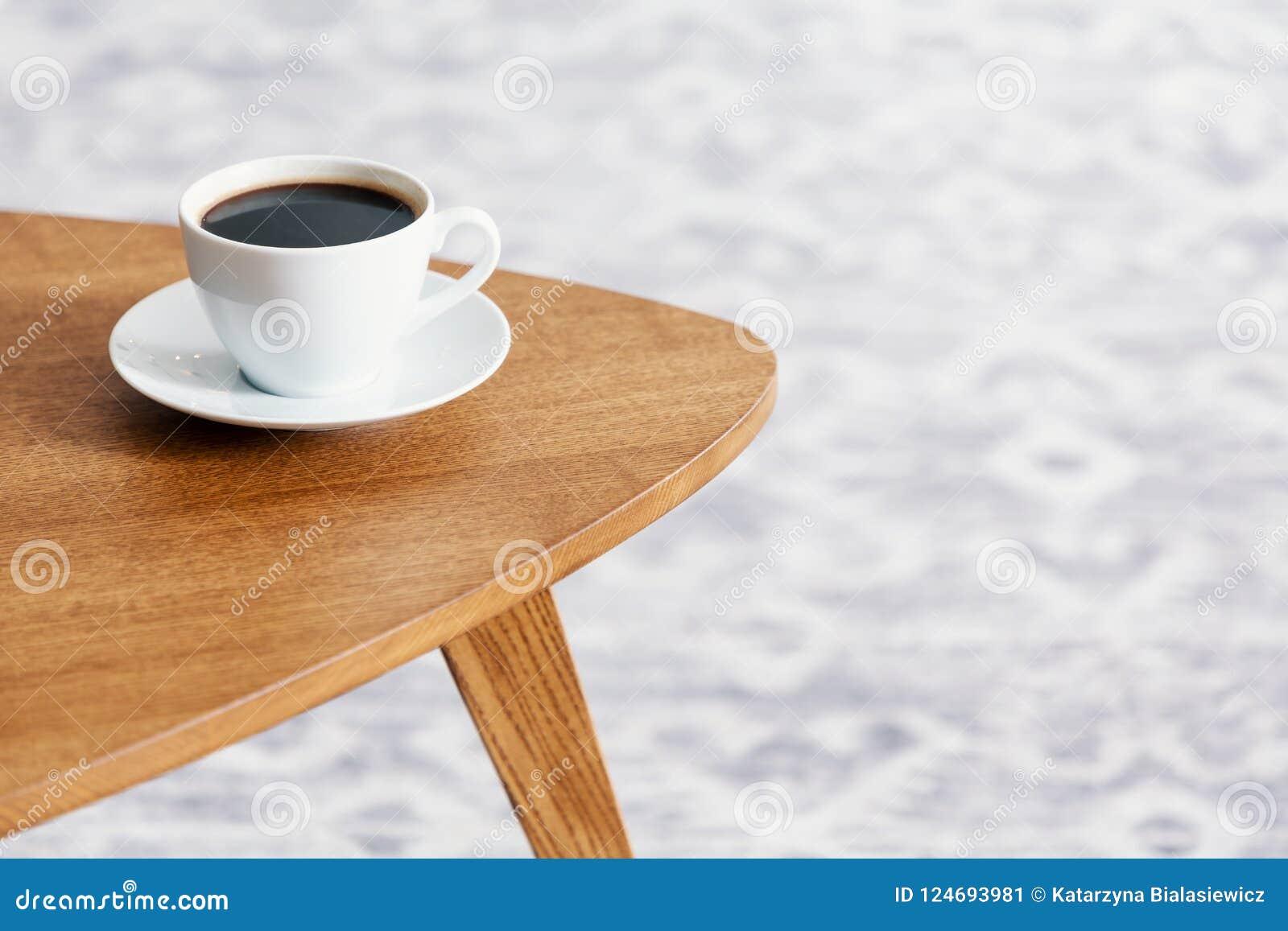 Primer de una taza de café en una tabla de madera