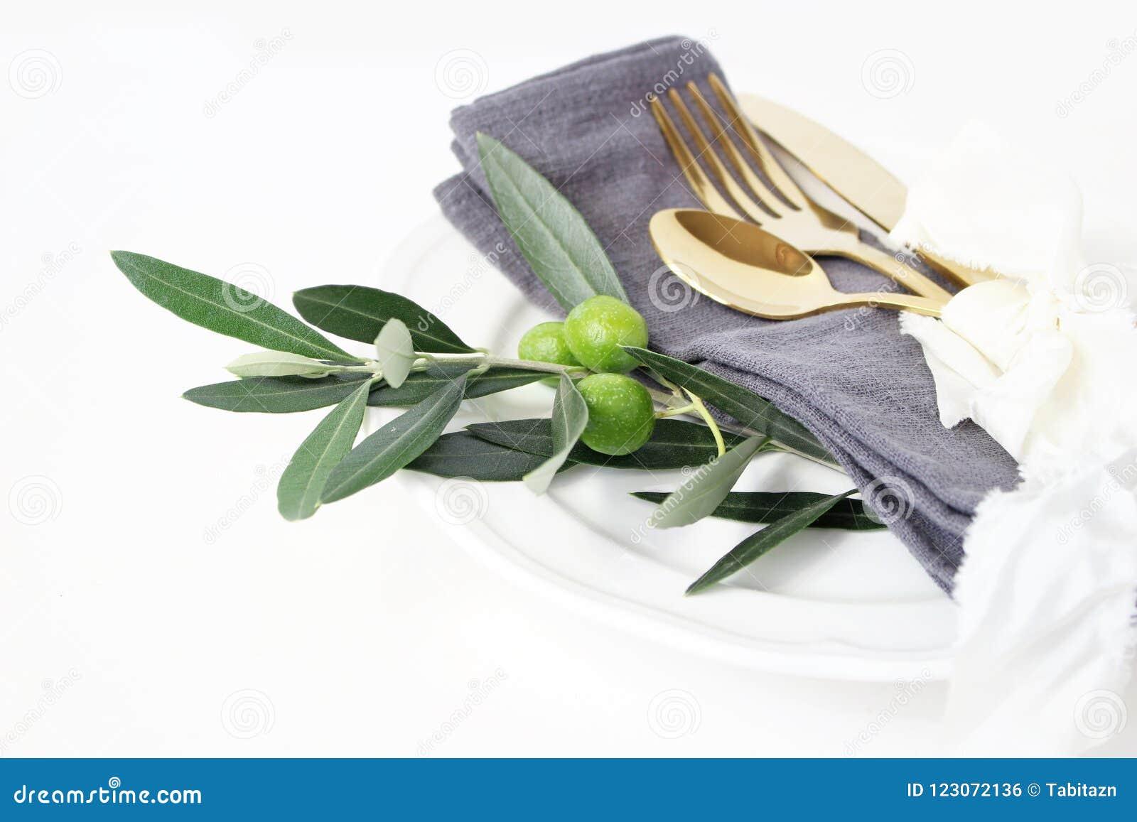 Primer del ajuste festivo del verano de la tabla con los cubiertos de oro, rama de olivo, servilleta de lino gris, placa de cena