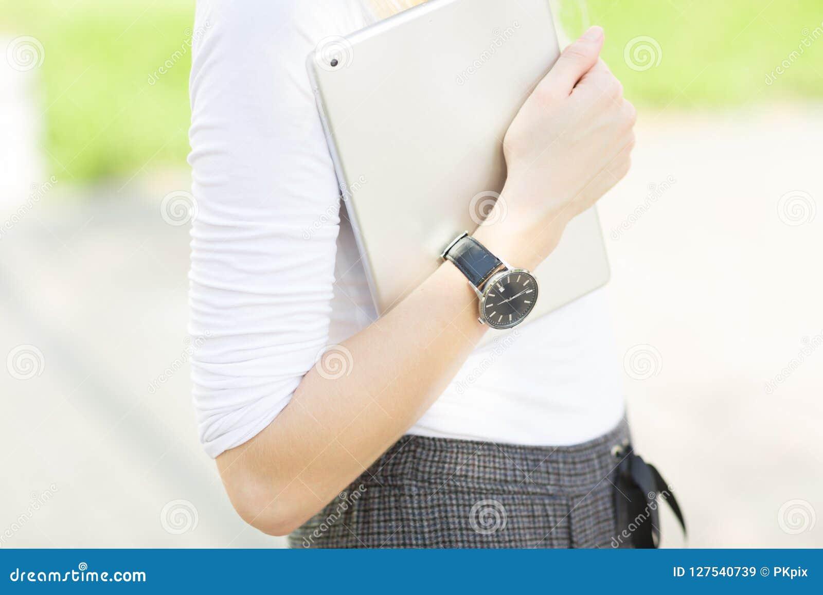 Primer del brazo femenino que lleva un reloj y que lleva una tableta digital al aire libre