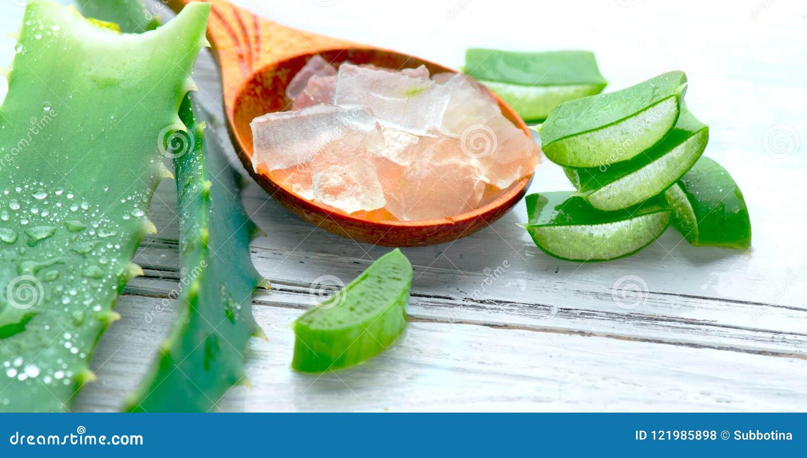 Primer del gel de Vera del áloe en el fondo de madera blanco Hoja y gel cortados orgánicos, ingredientes cosméticos orgánicos nat