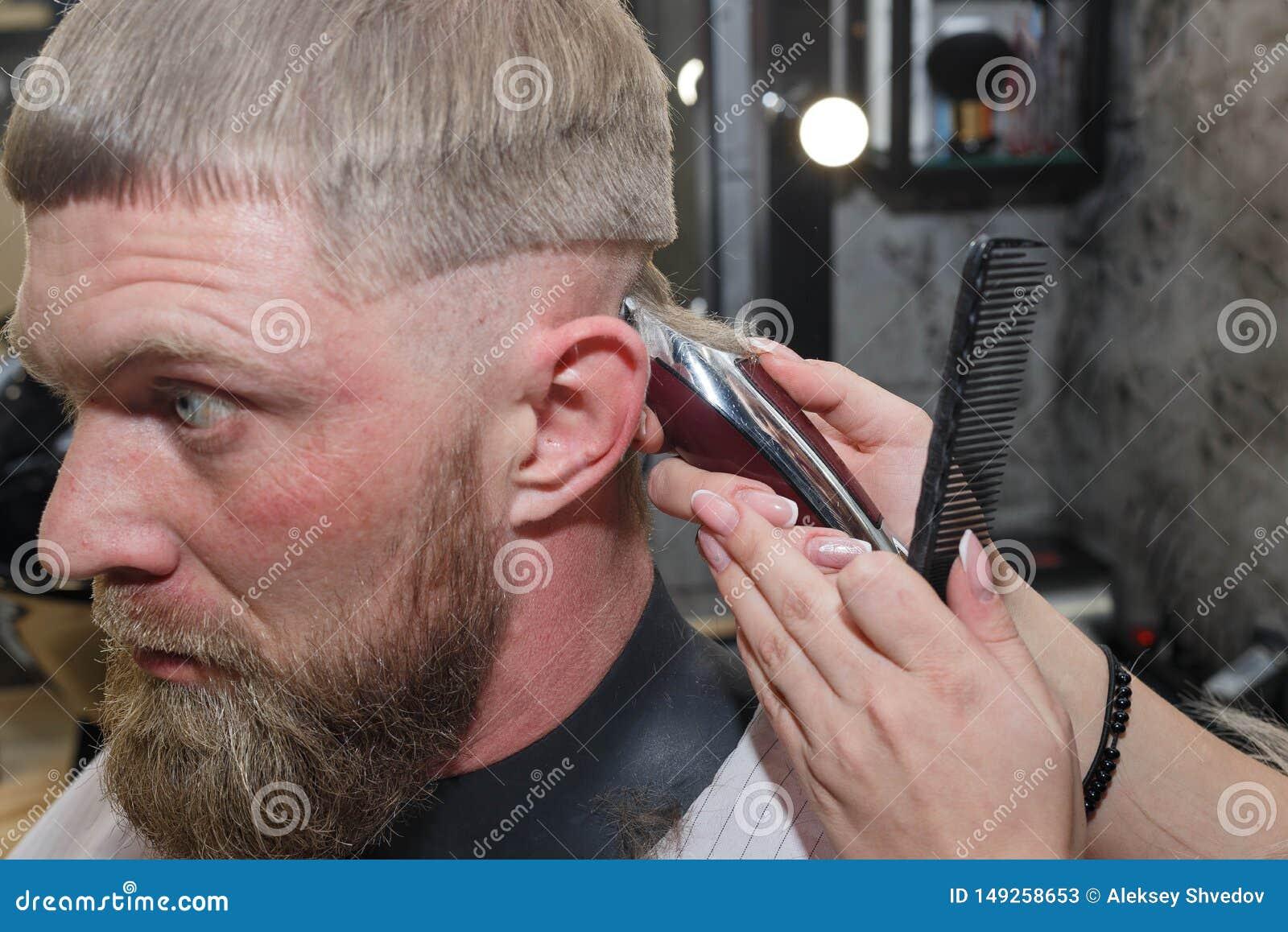 Primer del hombre de la m?quina de los cortes del peluquero en una barber?a