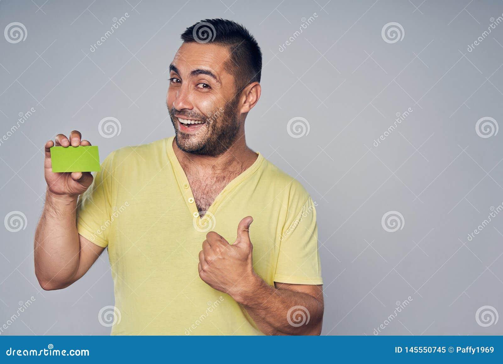 Primer del hombre hisp?nico casual que muestra la tarjeta del cr?dito en blanco
