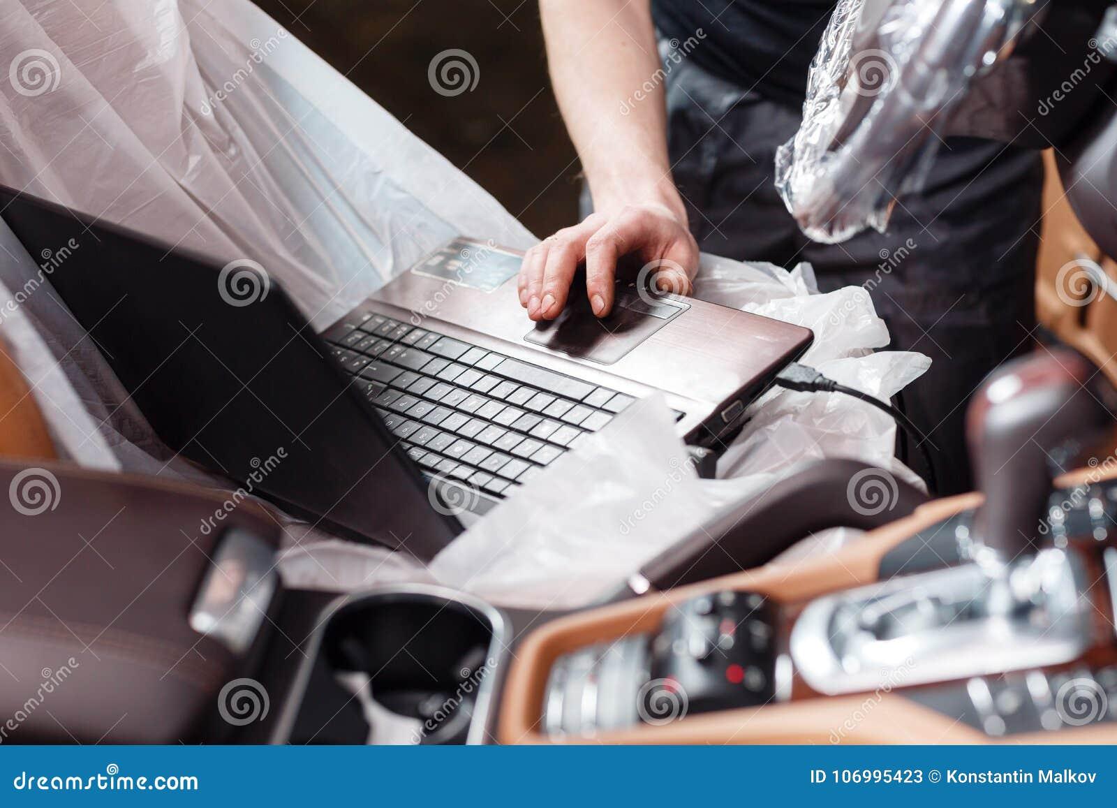 Primer del mecánico que usa el ordenador portátil digital mientras que examina el motor de coche en garaje conecte el conector de
