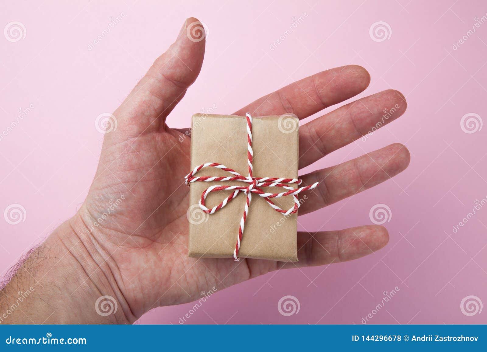 Primer del regalo Un regalo hermoso en la mano del hombre Fondo rosado