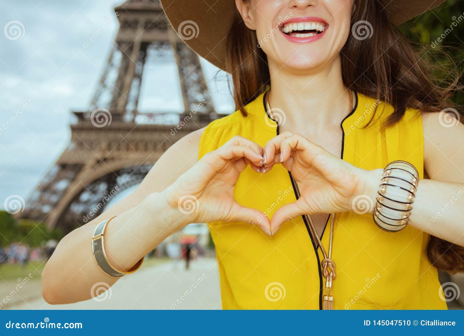 Primer en la mujer feliz del viajero que muestra las manos en forma de corazón