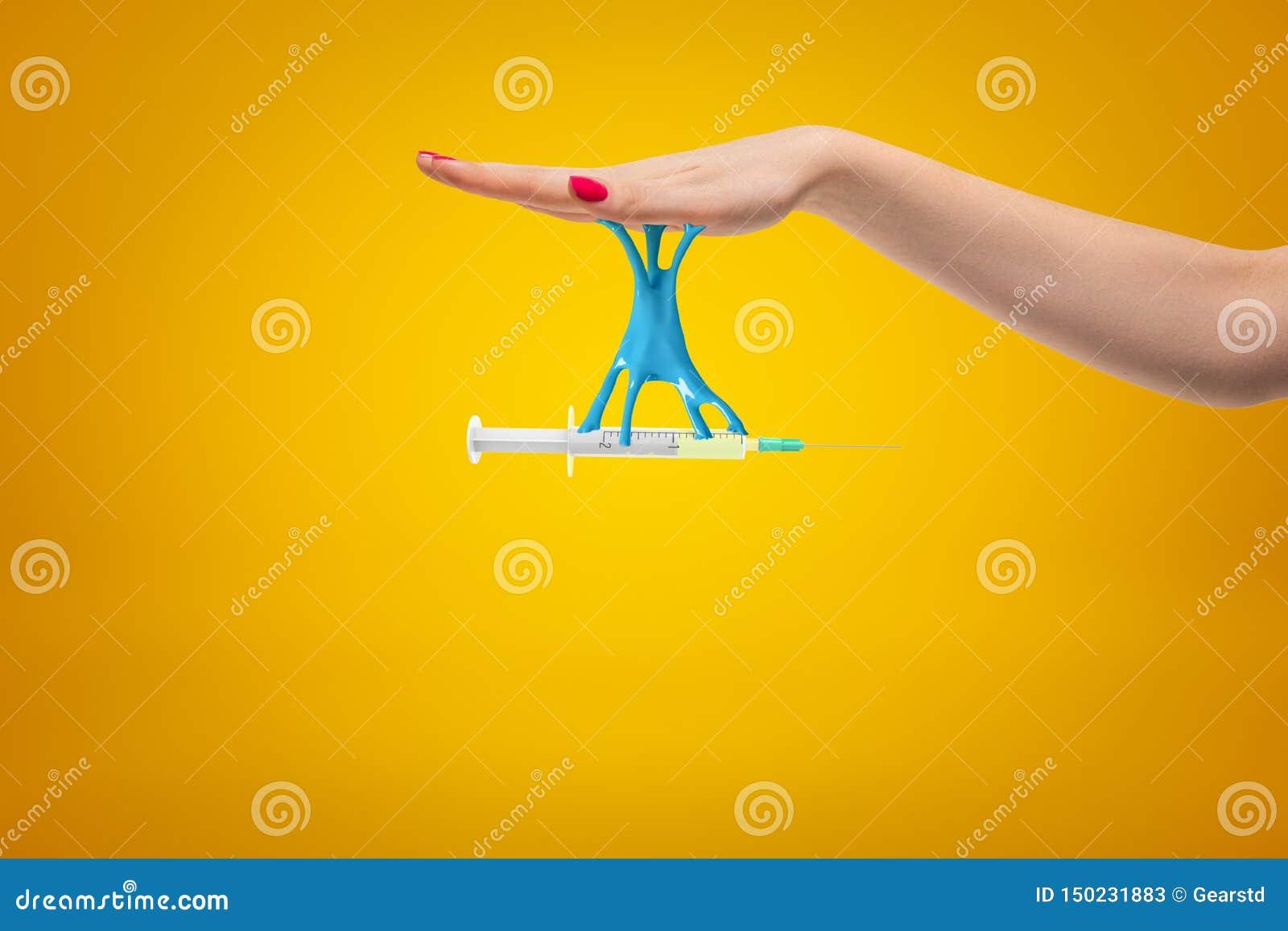 Primer lateral de la cosecha de la jeringuilla de la tenencia de la mano de la mujer que se pega a su palma con limo pegajoso azu
