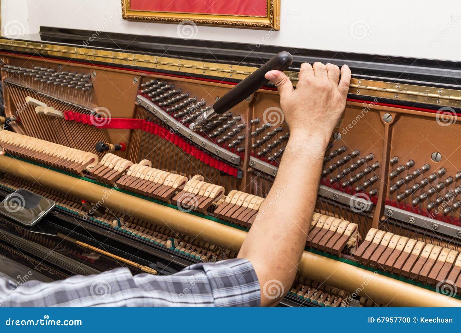 Primer a mano que adapta un piano vertical usando palanca y las herramientas