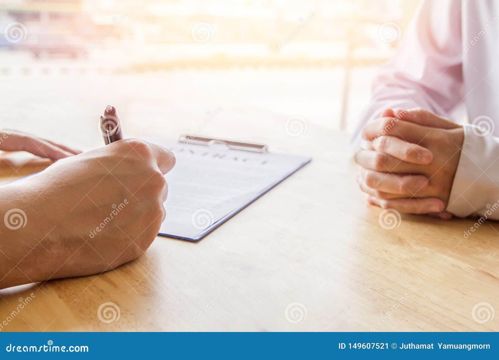 Primer Negocio asi?tico de la pluma de tenencia de la mano que revisa y que firma, contrato casero de la compra, foco selectivo