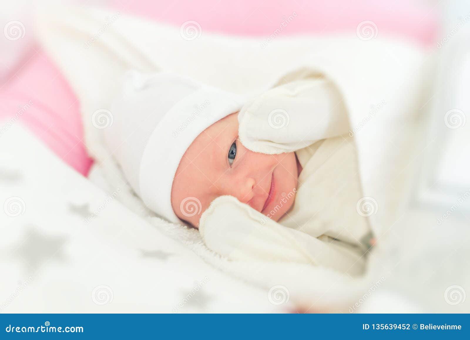 Primer soñoliento sonriente del bebé en una choza de bebé