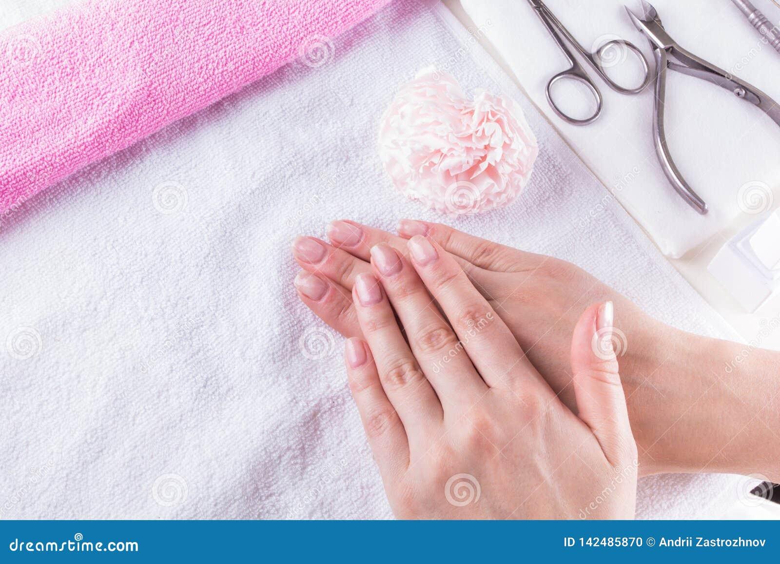 Primer tirado de manos femeninas con la manicura francesa en una toalla, sistema de manicura