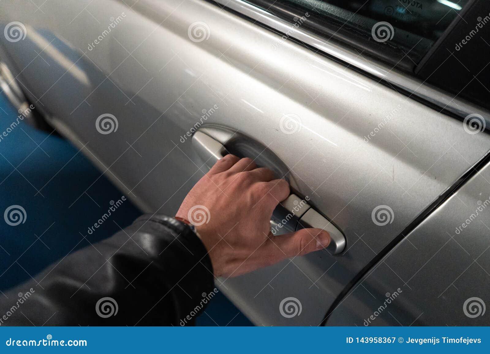 Primer una mano de los hombres en el cierre de una puerta de coche que lo abre encima - del coche del color claro