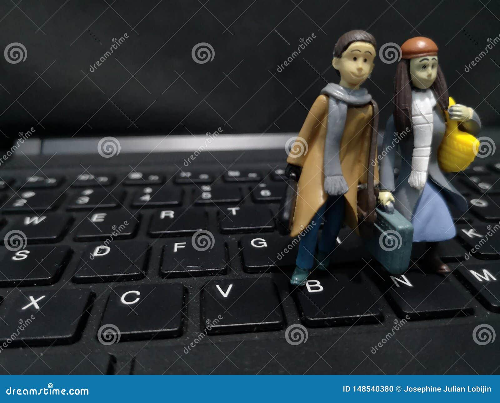 Primer y tiro macro de trabajadores miniatura con su maleta y un fondo del ordenador
