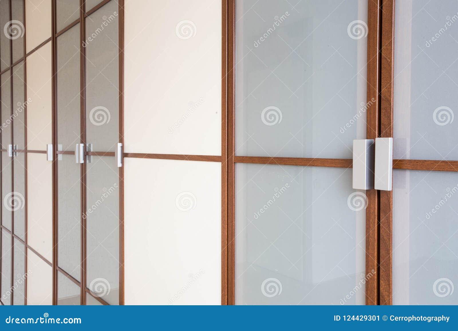 Primo piano bianco di legno delle porte di gabinetto per progettazione moderna dei vestiti nuova