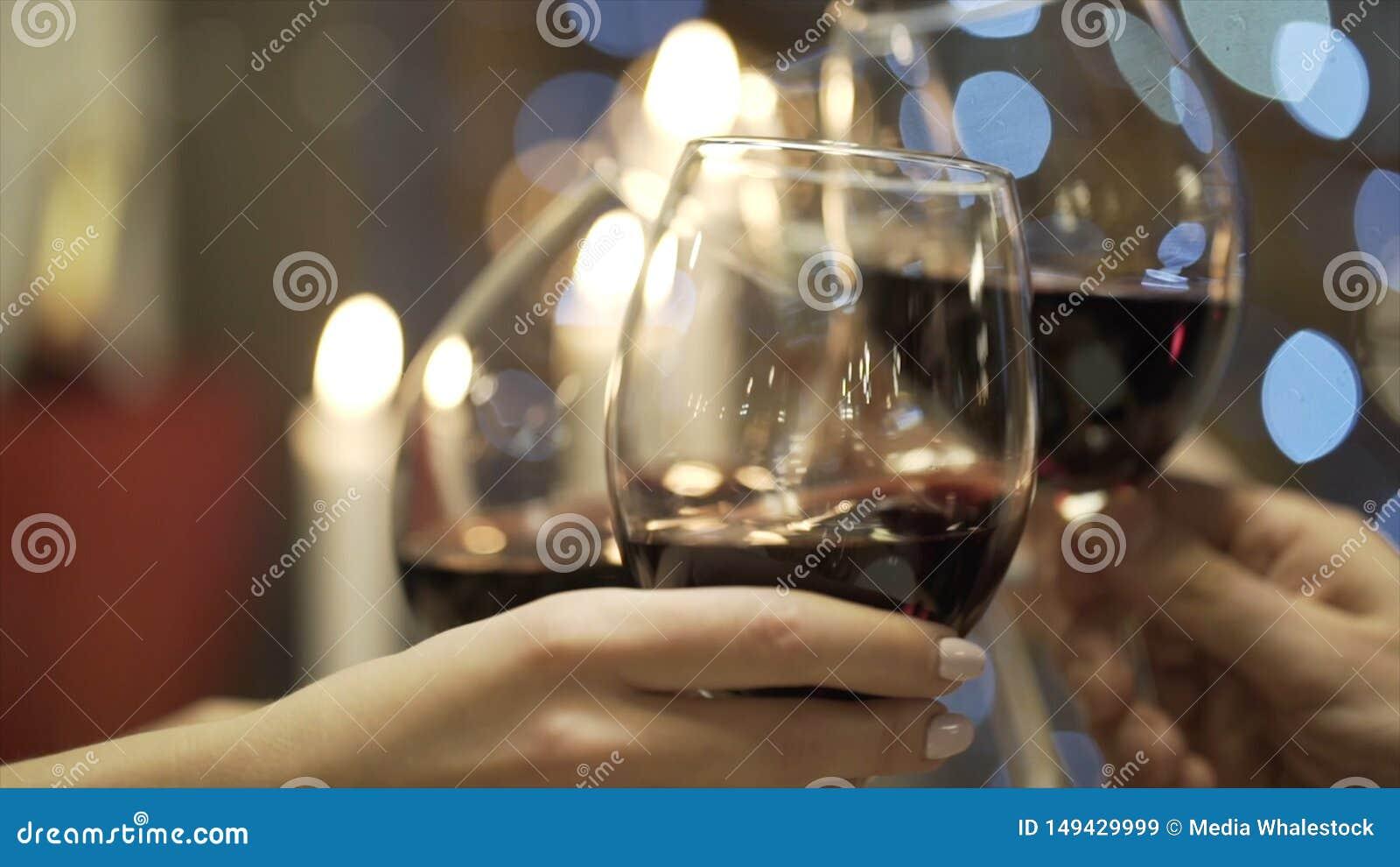 Primo piano degli amici vetri tintinnanti del champagne e del vino rosso nel ristorante azione Riunione del ` s dell amico