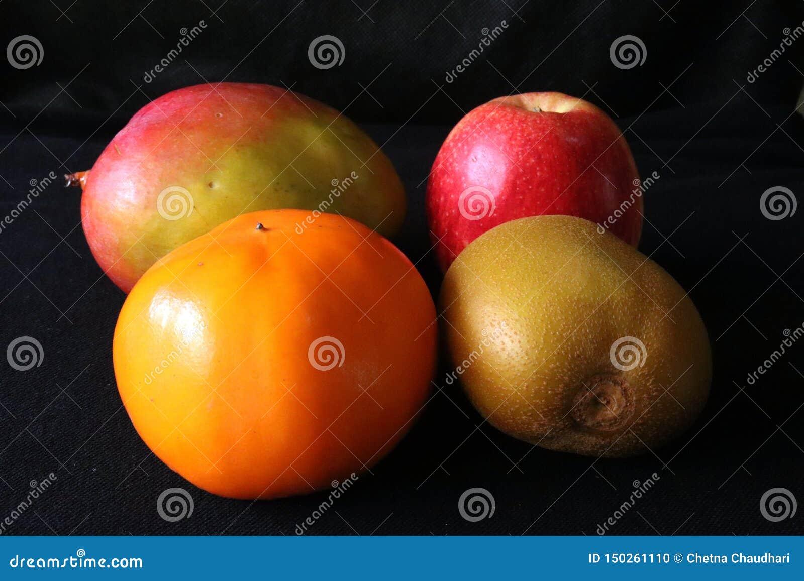 Primo piano dei frutti tropicali, mango, Apple, kiwi, cachi contro fondo nero