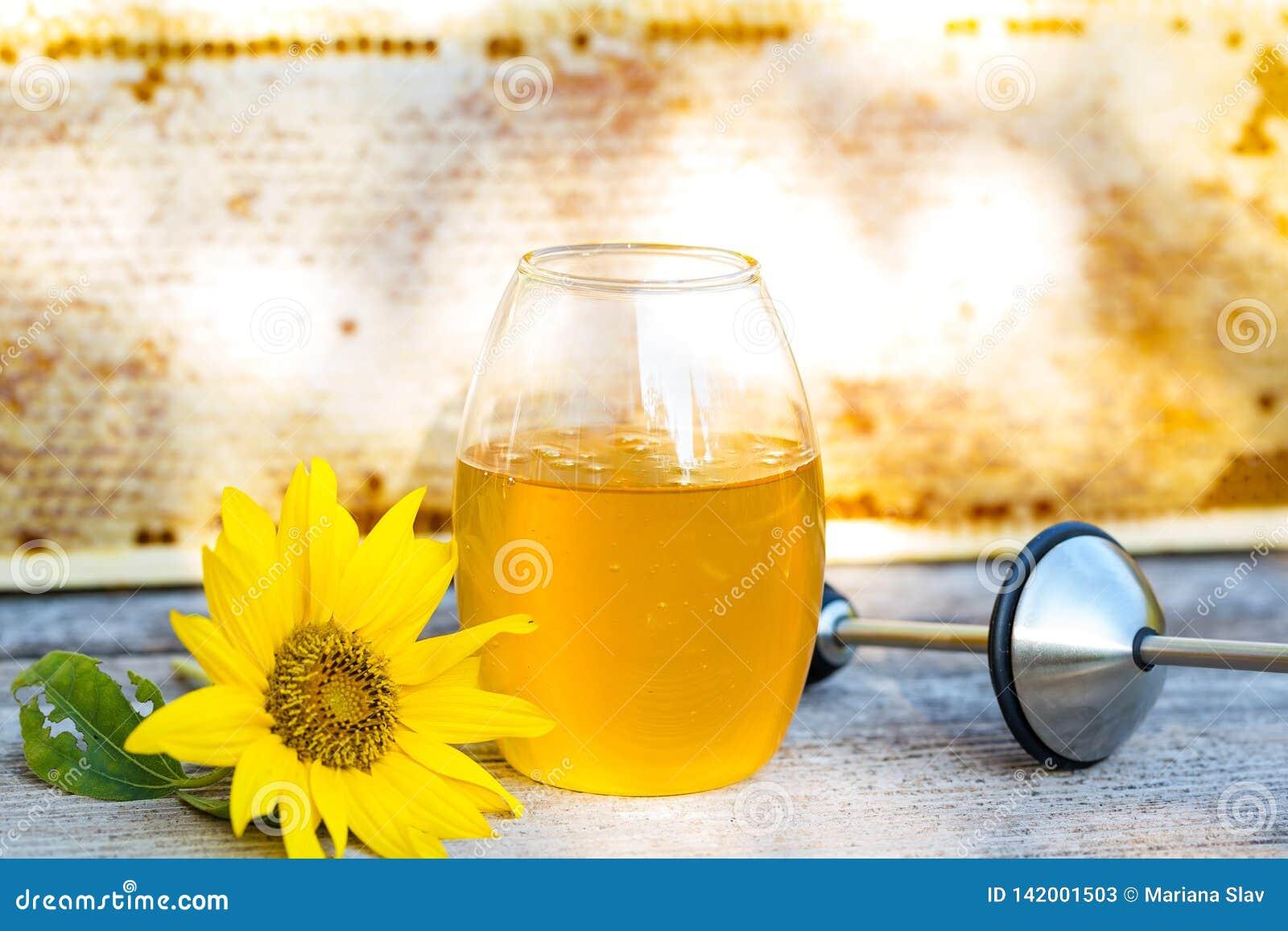 Primo piano del barattolo di miele e di un girasole