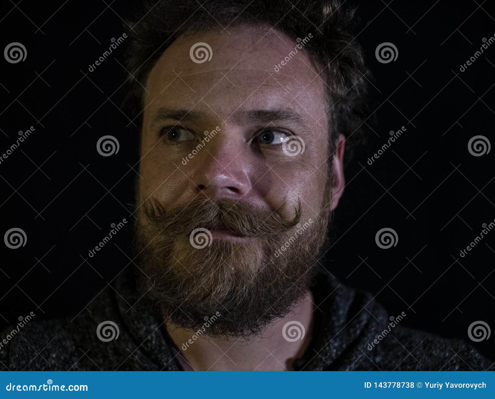 Primo piano del fronte di un uomo con i baffi e della barba su un backgrounde e su una barba neri