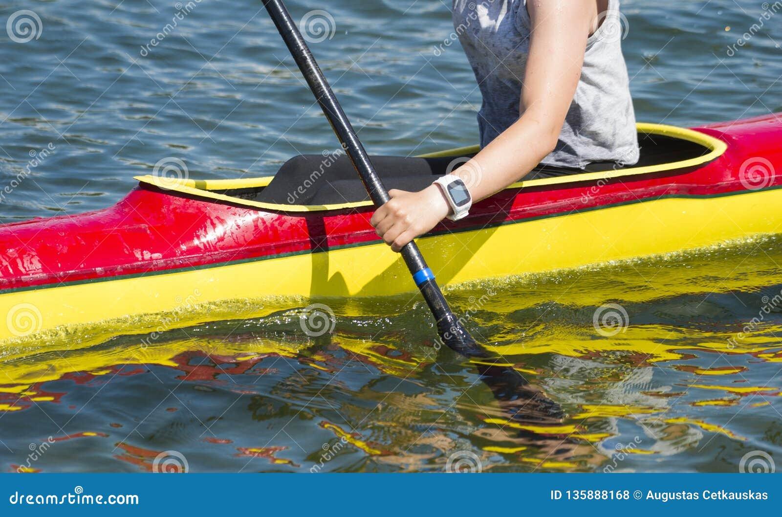 Primo piano del kayaker femminile che rema attraverso le rapide dell acqua