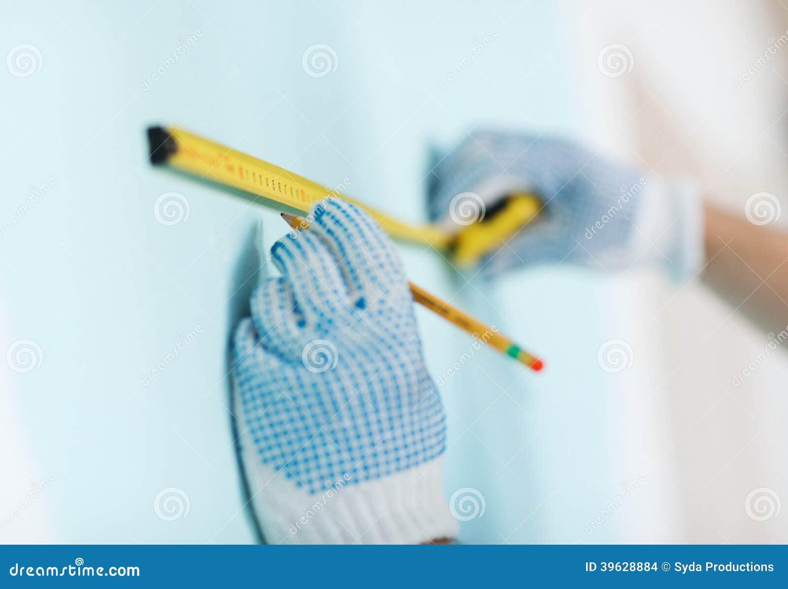 Primo piano del maschio in guanti che misurano parete con nastro adesivo