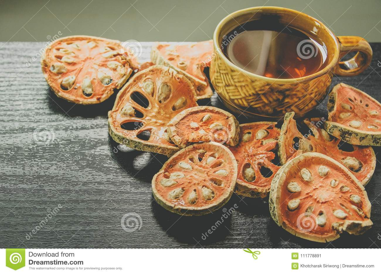 Primo piano del tè di cotogno del bengala e del succo asciutti e di vetro di cotogno del bengala sul pavimento di legno