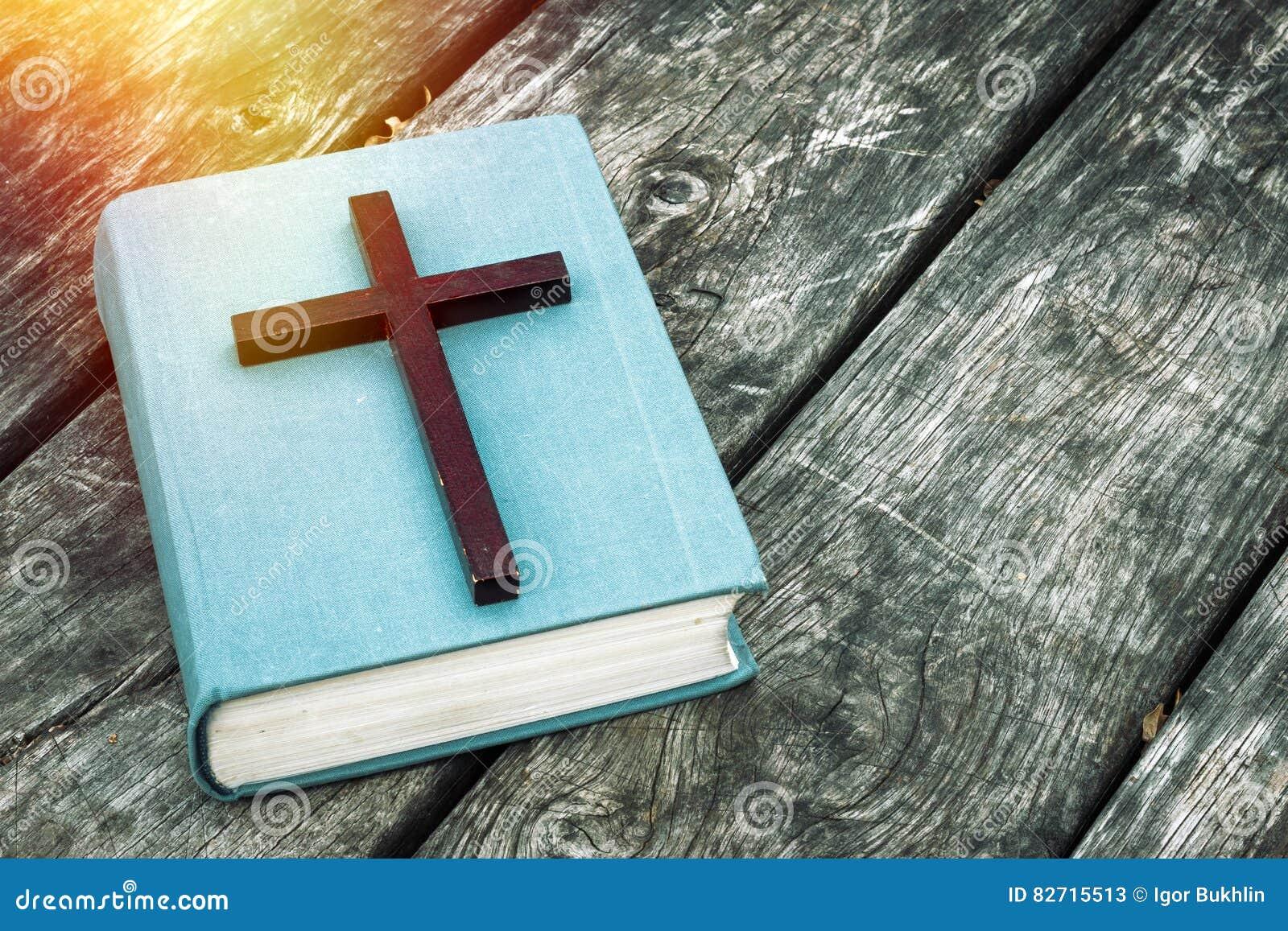 Primo piano dell incrocio cristiano di legno sulla bibbia, sulla candela bruciante e sulle perle di preghiera sulla vecchia tavol