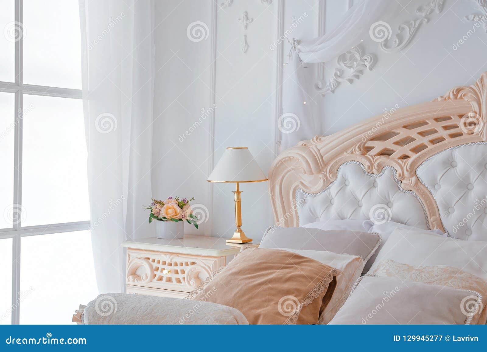 Primo piano della camera da letto bianca luminosa interna con la